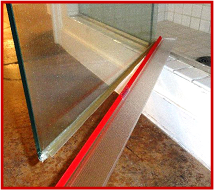 "Shower Door Drip Rail photo showing 3M-VHB Transparent Tape film liner partly removed and transparent drip rail. 36"" (.914m) length, 2"" flange."